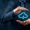 Cloud computing service concept – connect to cloud. Businessman offering cloud computing service represented by icon. Wide banner composition and bokeh in background.